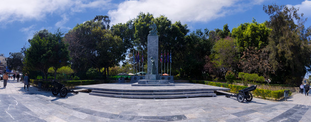 Heraklion, Crete Island / Greece. Monument of the Batlle of Crete (World War 2) at Georgiadi's park in the center of Heraklion city. Panoramic view on a sunny day with cloudy sky