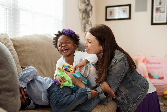 Smiling mother playing with children on sofa at home
