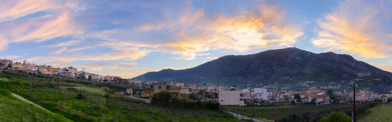 Archanes, Crete Island / Greece. Panoramic view of Archanes town at sunset time. Sun has just went down behind Juktas mountain giving to the cloudy sky beautiful colors