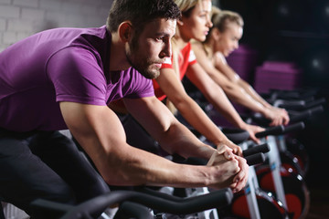 Papiers peints Fitness Close up hands of man biking in spinning class. Group of smiling friends at gym exercising on stationary bike. Happy cheerful athletes training on exercise bike.
