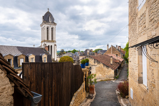 Narrow street of Montignac with a view of the church tower rising above the village