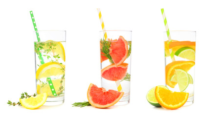Variety of citrus infused detox water drinks in glasses with paper straws isolated on a white...