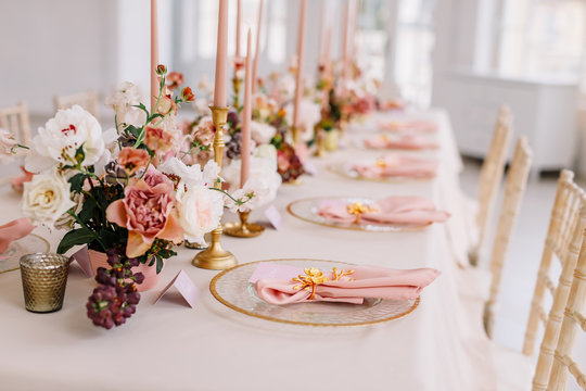 Wedding decoration table in the hall, floral arrangement. In the style vintage. Decorated dining table with flowers for guests and newlyweds, in peach-pink & pastel color. Beautiful table setting.