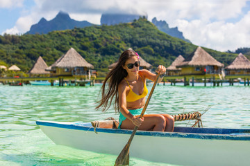 Wall Mural - Outrigger Canoe - woman paddling in traditional French Polynesian Outrigger Canoe for recreation sport watersport competition. Bora Bora with Mount Otemanu and overwater bungalow resort hotel.