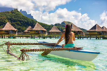 Wall Mural - Outrigger Canoe - woman paddling in traditional Polynesian Outrigger Canoe