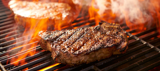 Aluminium Prints Steakhouse rib-eye steaks cooking on flaming grill panorama
