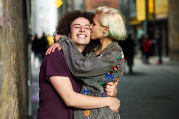Young couple hugging in urban background on a typical London street.