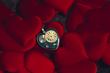 pendant in the form of a heart and the clockwork inside lies on the heart-shaped pads; idea for an image of time and love