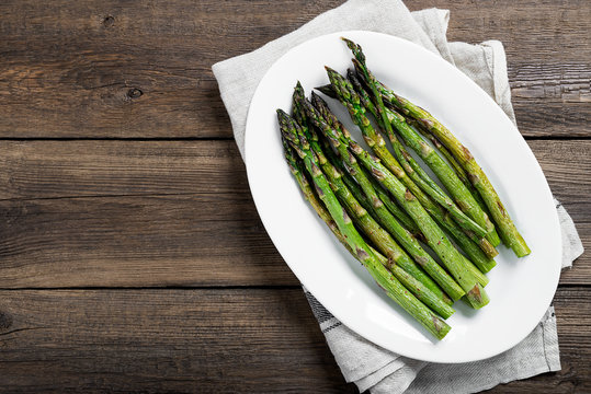 Grilled green asparagus on white plate. top wiew