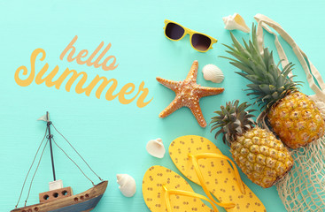 Autocollant pour porte Plage Ripe pineapple and beach sea life style objects over pastel mint blue wooden background. Tropical summer vacation concept