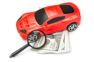 Magnifying glass with red car toy and money on white.