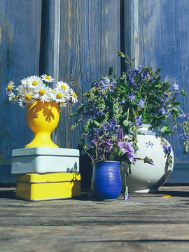 Floral composition of wild flowers and old cans, on blue wooden veranda background, outdoor, morning garden scene, natural light and shadows, daylight. Colorful still life in rustic style. Vertical
