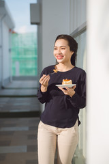 Young happy woman stands on the terrace of the hotel with dish cake in the morning. Pretty asian girl in good mood and is ready for adventures.