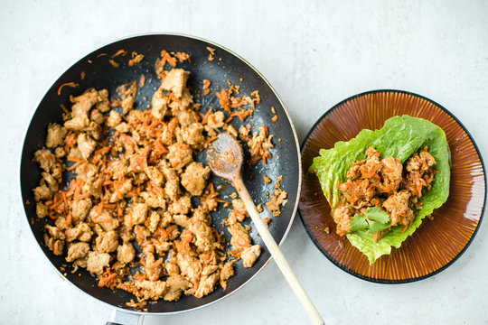 Top view of frying pan with cooked/sauteed ground turkey with shredded carrots and sweet soy sauce and lettuce cups finger food on a brown pottery plate. Overhead, close up.