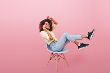 Shapely black woman in vintage denim pants chilling on comfortable chair. Indoor photo of curly amazing girl in black shoes having fun during photoshoot.
