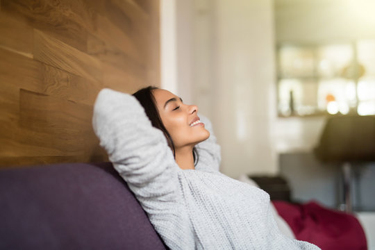 Young relaxed smiling young woman lying on couch