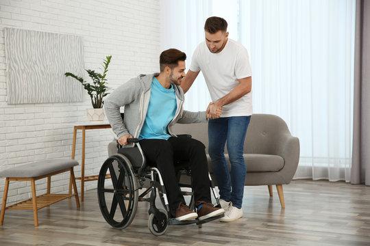 Volunteer helping man in wheelchair at home
