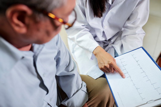 Close-up of senior man and doctor with cardiogram on clipboard meeting in medical office at hospital, doctor explaining some facts about disease