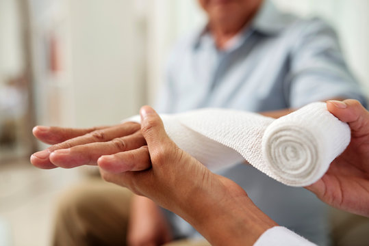 Close-up of nurse holding and bandaging hand of senior patient at hospital