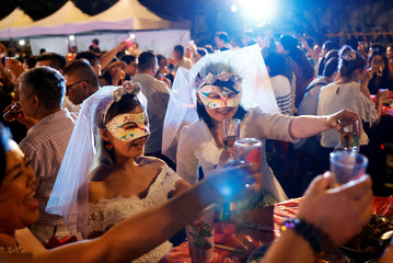 A newlywed lesbian couple celebrates during a mass wedding banquet, one day after same-sex marriage officially became legal, in Taipei