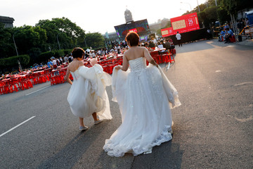 A newlywed lesbian couple in wedding dresses attends a mass wedding banquet, one day after same-sex marriage officially became legal, in Taipei