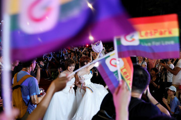 A newlywed lesbian couple wave to supporters during mass wedding banquet, one day after same-sex marriage officially became legal, in Taipei