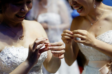 A newlywed lesbian couple exchanges wedding rings during a mass wedding banquet, one day after same-sex marriage officially became legal, in Taipei