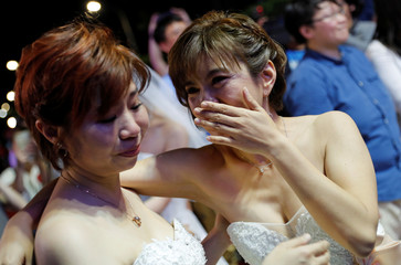 A newlywed lesbian couple reacts during a mass wedding banquet, one day after same-sex marriage officially became legal, in Taipei