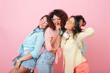 Graceful asian girl with backpack posing beside friends during joint photoshoot in pink studio. Indoor photo of african glamorous lady telling secret to brunette female models.