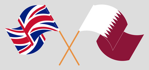 Crossed and waving flags of the UK and Qatar