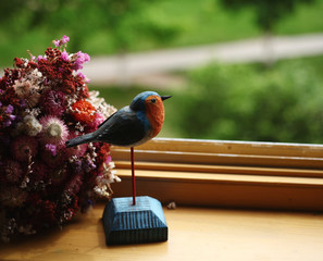 souvenire wooden figure of little bird robin   and a bouquet on the windowsill against nature spring background