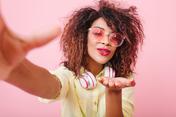 Cheerful stylish african girl wears cute sunglasses sending air kiss while making selfie at home. Portrait of happy black lady in yellow enjoying good day and taking picture of herself.
