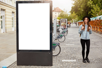 Thoughtful female tourist strolls on footway near lightbox with mock up blank space for your...