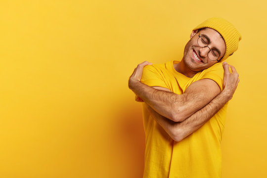 Pleased Caucasian man hugs himself, has high self esteem, tilts head, has toothy smile, wears casual yellow hat and t shirt, stands indoor, copy space for your promotional content, feels comfort