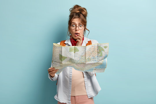 Half length shot of scared embarrassed woman looks stressfully at map, afraids of being lost, wears optical glasses, casual outfit, stands over blue background. Tourism, destination concept.