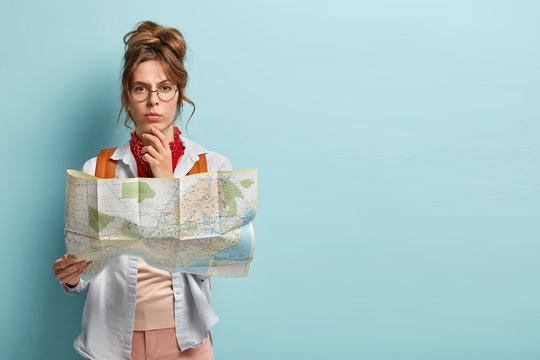 Studio shot of serious thoughtful female tourist holds chin, plans her trip, holds paper map, wears transparent glasses, looks straightly at camera, stands against blue background with free space