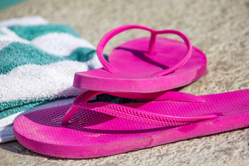 Pink slippers and towel on a pool deck