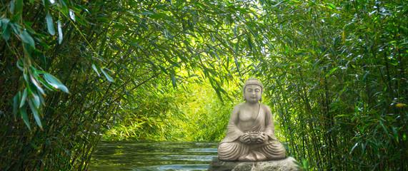 buddha auf einem stein im wasser im bambuswald