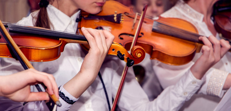 Children play violins during the concert. Performing Classical Music on Violins_