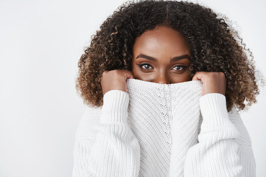 Winter cannot get me in this sweater. Portrait of charming and sensual african-american woman with seductive gaze pulling collar of clothes on face to warm-up and hide from weather over white wall