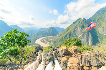 Couple trekking boot on mountain top at Nong Khiaw panoramic view over Nam Ou River valley Laos  travel destination in South East Asia, people traveling millenials concept