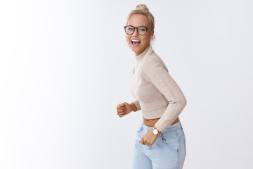 Come on dance with me. Portrait of charming carefree stylish european female with combed hair dancing and singing happily smiling broadly enjoyong awesome music party over white background