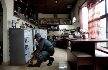 Sri Lankan army soldiers search a house during a special cordon and search operation conducted by the military in Sri Lanka's capital Colombo and suburbs, five weeks after Easter Sunday bomb attacks, in Mattegoda
