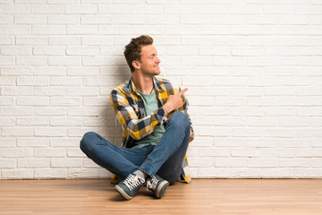 Blonde man sitting on the floor pointing back