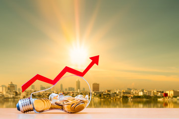 Coin in the bottle of light bulb and arrow graph with growing value money put on the wood on photo blur cityscape on sunlight background, Business investment and saving energy concept.