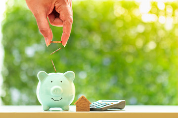 Woman hand hold a coin with save in the piggy bank and wooden home model for family and calculator on sunlight in the public park, Loan for buy a new house and real estate concept Wall mural