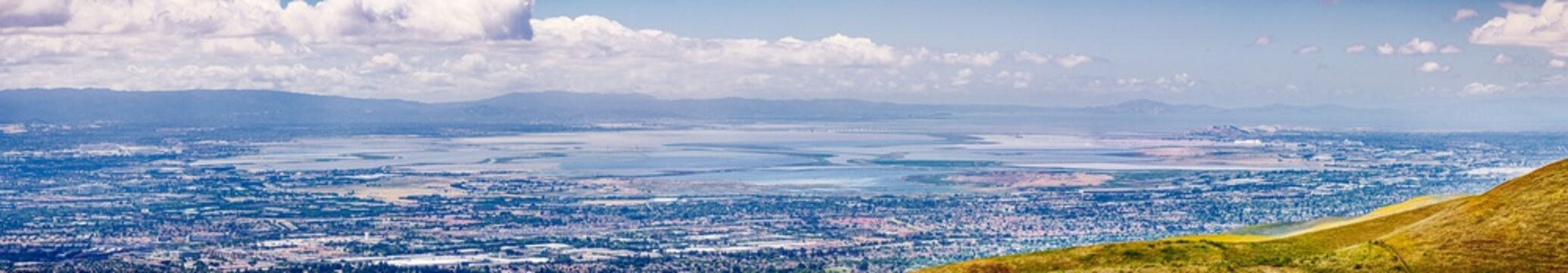 Panoramic view of the cities on the shoreline of south San Francisco bay area; colorful salt ponds in the background; Silicon Valley, California