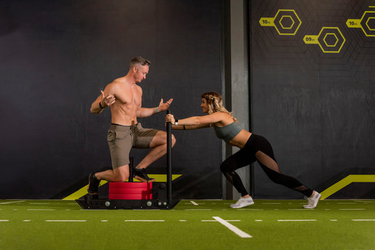 Male and Female workout partners with male standing showing his six pack abs on the weighted sled as his female partner pushes
