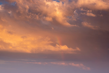 Sunset clouds with orange light and rainbow