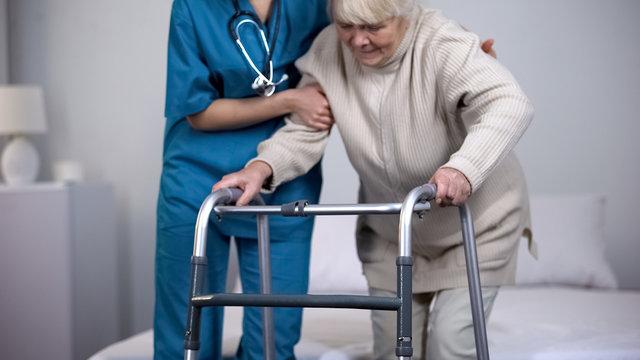 Nurse assisting patient walking frame, hip joint replacement rehabilitation